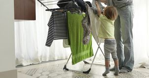 Little boy helping hang laundry his mother stock video