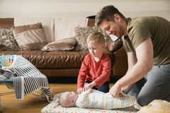 Little Boy Helping His Dad with the Baby. Little boy helping his father change his baby brother. They are both sitting on the floor in the living room stock image