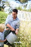 Little boy helping his father watering plants Stock Photos
