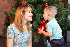 Little boy helping his mom to decorate christmas tree. Stock Image