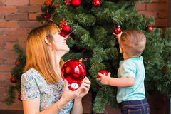 Little boy helping his mom to decorate christmas tree. Stock Photo