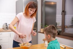 Little boy helping his mother with the cooking in the kitchen royalty free stock photo
