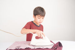 Little boy helping house work using iron his cloth Stock Images