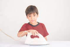 Little boy helping house work using iron his cloth Royalty Free Stock Images