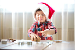 Little boy helping at kitchen with baking cookies Stock Photos