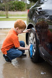 Little boy helping wash his father's car Royalty Free Stock Images