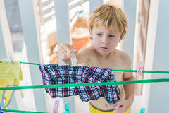 A little boy helps her mother to hang up clothes Stock Photo