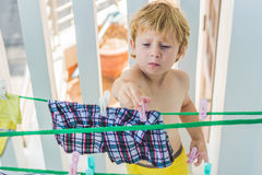 A little boy helps her mother to hang up clothes Royalty Free Stock Photography