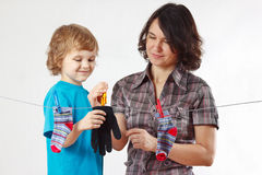 Little boy helps her mother to hang up your glove and socks Royalty Free Stock Photos