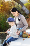 Little boy with her mother on the autumn lake Royalty Free Stock Photo