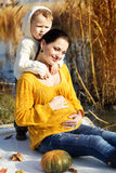 Little boy with her mother on the autumn lake Stock Photography
