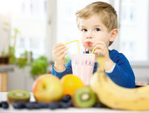 Little Boy heureux buvant un Smoothie sain dans sa maison confortable, W Photos stock