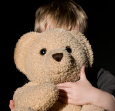 Little boy hidden behind a bear Royalty Free Stock Images