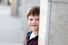 Little boy hide and seek behind pillar Royalty Free Stock Photography