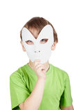 Little boy hides his face behind mask Stock Photo