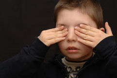 Little Boy Hiding. Young boy with his hands covering his eyes, serious expression. Isolated on dark background stock photo