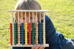 Little boy hiding behind an abacus. Little boy hiding behind the colorful abacus and watching thru royalty free stock image
