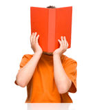 Little boy is hiding behind a book. While sitting at table, isolated over white Royalty Free Stock Photo