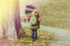 Little boy hiding behind colorful umbrella outdoors. Playful little child boy hiding behind colorful umbrella outdoors Royalty Free Stock Photography