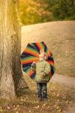 Little boy hiding behind colorful umbrella outdoors. Playful little child boy hiding behind colorful umbrella outdoors Royalty Free Stock Image