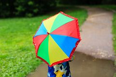 Little boy hiding behind colorful umbrella Stock Image