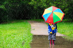 Little boy hiding behind colorful umbrella outdoors Stock Photography