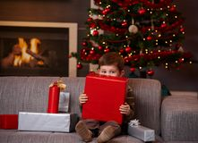 Little boy hiding behind gift box at christmas. Little boy sitting on couch hiding behind gift box, looking over it Royalty Free Stock Photo