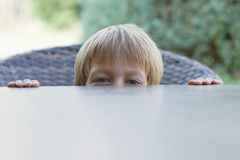 Little boy hiding behind the table Royalty Free Stock Photo