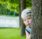 Little boy hiding behind tree Royalty Free Stock Photo