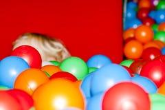 Little boy hiding behind two plastic balls. Little boy hiding behind two green plastic balls Royalty Free Stock Photo