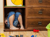 Little boy hiding in a cupboard Royalty Free Stock Photography