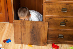Little boy is hiding in the cupboard Royalty Free Stock Photos