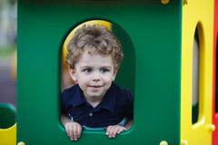Little boy hiding in a playhouse Stock Photo