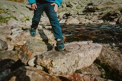 Little boy hiking in mountains crossing waterfall, focus on boots. Little boy hiking in mountains crossing waterfall, on boots, travel concept royalty free stock photo