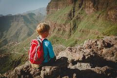 Little boy hiking in mountains looking at view. Family travel concept royalty free stock photography