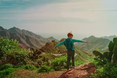 Little boy hiking travel in mountains looking at view. Family travel stock image