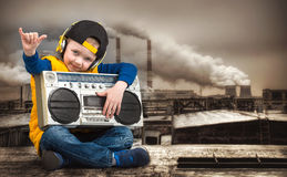 Little boy in Hip-Hop listens to the old tape recorder. The Young Rapper.Cool rap DJ.Vintage silver boom box Radio.Children`s fash. The Young Rapper.Graffiti on royalty free stock image
