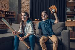 Little boy and his beautiful mother sitting on couch in living room with baseball bat and mitt while