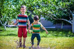 Little boy and his brother play in summer park. Children with colorful clothes jump in puddle and mud in the garden. Kids walk in summer puddle after shower Stock Images