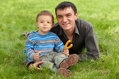 Little boy and his dad. A dad and his little son are playing in the park royalty free stock image