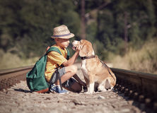 Little boy with his dog sitting on the railway Royalty Free Stock Photos