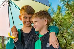 The little boy and his elder brother are under a bright multi-colored umbrella royalty free stock photos