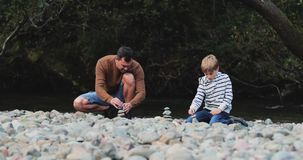 Building Cairns with Dad. Little boy and his father are building cairns in the Lake District while out hiking stock video footage