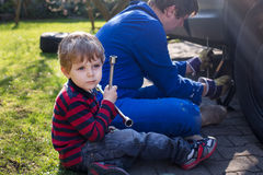 Little boy and his father changing wheel on car Stock Images