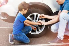 Little boy and his father changing wheels on a car Royalty Free Stock Images