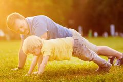 Little boy and his father doing plank exercise in sunny summer park. Outdoor sport activities for family with kids stock photo