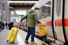 Little boy and his father go in express train on railway station platform Stock Photo
