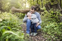 Little boy and his father on grass in autumn forest. A Little boy and his father on grass in autumn forest royalty free stock image