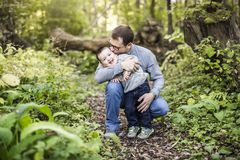 Little boy and his father on grass in autumn forest. A Little boy and his father on grass in autumn forest royalty free stock images