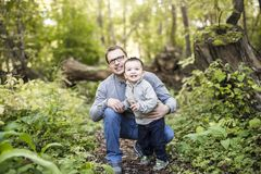Little boy and his father on grass in autumn forest Stock Photo